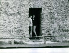 Two women standing together smiling in a door of a stone building. 1962.