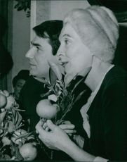 Robert Hossein with a woman, looking away.