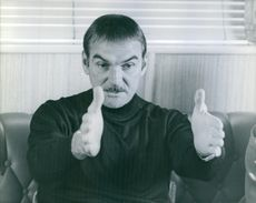 Sir William Stanley Baker sitting and indicating something with hand.