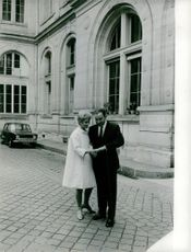 Rene Ribiere with his wife standing and holding hands outside the building.