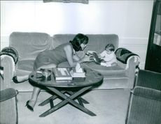 A woman with a child on a couch. 1962