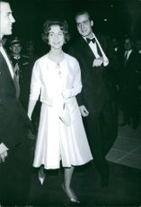 Juan Carlos and Queen Sofia walking together, smiling.
