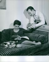 A photo of Rossana Podestà sitting and reading a book.