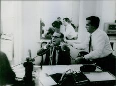 A man on a microphone answering 2 phones at one time while another man is assisting him. April 8, 1964.