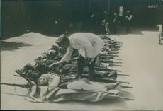 A soldier feeding the wounded people lying on stretchers.1936