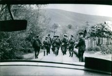 """A group of soldiers walking along a street seen from a vehicle.  """"China - Soviet Soviet troops in China""""  1969"""