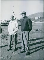 Juan Peron standing at beach with another man and smiling.