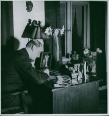 Einar Beyron sitting in front of the table writing, 1937.