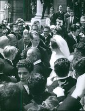 Carlos Hugo, Duke of Parma and Piacenza and Princess Irene of the Netherlands surrounded by people on their wedding day.