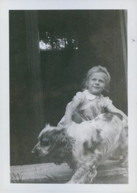 Brita Ulich with her dog Jimmie playing on the playhouse.