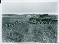 Soldiers with tanks in a field.