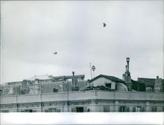 Two military helicopters hovering over the building in Alger. 1940