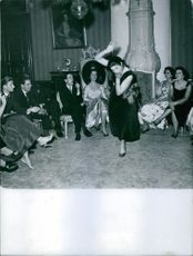 Marie Thérèse, Duchess of Württemberg and Henri d'Orléans, Count of Paris, Duke of France, watching a woman perform at a party.
