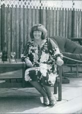 Mrs. Charmain Biggs sitting on a chair while smiling, 1976.