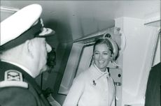 Queen Paola of Belgium with an officer, smiling.
