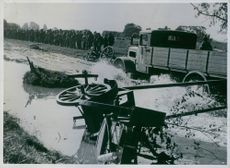 Soldiers armed truck trapped in the muddy field, soldiers standing aside and looking.  1939