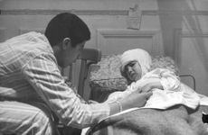 A kid is sick lying in bed during Algerian War in France. 1962
