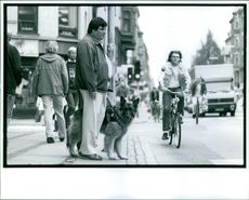 Man standing with dog on sidewalk, people passing by.