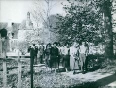 Princess Margarita walking in garden with other people while communicating with them.1964
