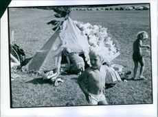 Children playing around their tent in an open field.