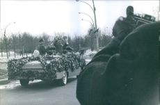 Leonov and Belyaev passing by the street and waving and smiling.