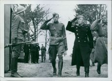 Soldiers looking at the guard saluting while entering a camp in Sweden during German occupation of Denmark, 1940.