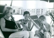 Caterina Valente playing cards with a child and another woman. Photo taken on August 2, 1967.