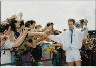 John McEnroe receives the audience's tribute with the cup in his hand after winning the double with Michael Stich in Wimbledon in 1992