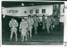 Rescued oilmen stepping gratefully on to the tarmac.
