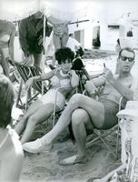 Fred MacMurray having fun with other people at beach and smiling.