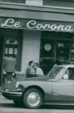 Couple sitting in roadside cafe and car parked in front.