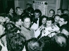 Renata Tebaldi surrounded by fans, giving autograph. 1959