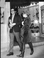 Roger Vadim walking with a woman.