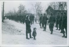 Soldiers marching in street, a woman standing with her little kid looking at them.1944