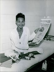 Man sitting on bed, holding newspaper in hands and showing it to the camera.