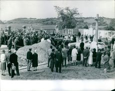 People gathered at cemetery for death ceremony.