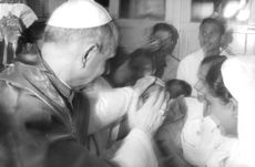 Pope Paul VI blessing a child inside a hospital.