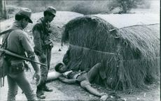 A wounded man lying on ground, soldiers standing beside looking at him.