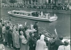 People waving to Princess Beatrix standing on boat.