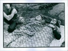 Three youngsters relaxing and sleeping on the ground.