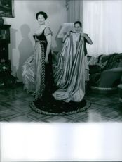 Renata Tebaldi getting help to get dressed from a lady.