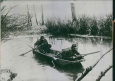 Two men riding a rowing boat and tries to take cover while one of them holds a rifle, 1915.