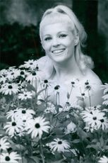Woman posing with flowers, smiling.