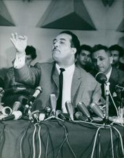 Kaïd Ahmed sitting in front of a table with microphones, gestures his hand as he speak, 1965.