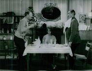 Two men standing and quarreling during the dinner, woman siting.
