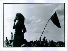 A woman standing in the crowd.