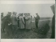 Soldiers standing together while looking a map during World War I.