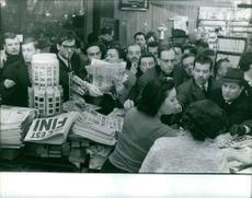 People purchasing newspaper.