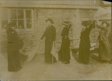 1915 Women walking on road, holding flags.