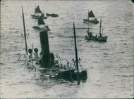 A ship sinking in sea, few other boats floating.